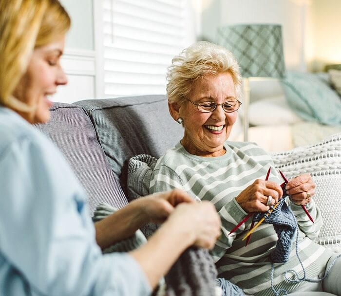 Two smiling women knitting
